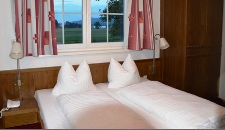 Schlafzimmer mit Doppelbett, Nachtkästchen mit Lampen, Tisch und Stühle, Kasten