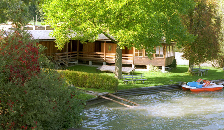 im Vordergrund der See - seitlich ein Tretboot, im Hintergrund die Liegewiese und eine Badehütte, Sträucher und Bäume