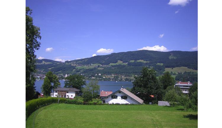 Aussicht vom Haus auf die Wiesen, Häuser, im Hintergrund der See und die Berge
