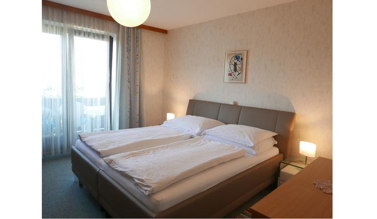 Schlafzimmer mit Doppelbett, Nachtkästchen mit Tischlampen, seitlich eine Balkontür