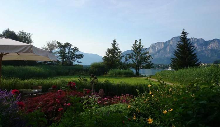 Blick über den Garten zum Mondsee, im Hintergrund die Berge. (© Seehotel Lackner)