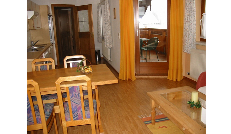 Dining area, table with chairs, kitchen, in the background a balcony door