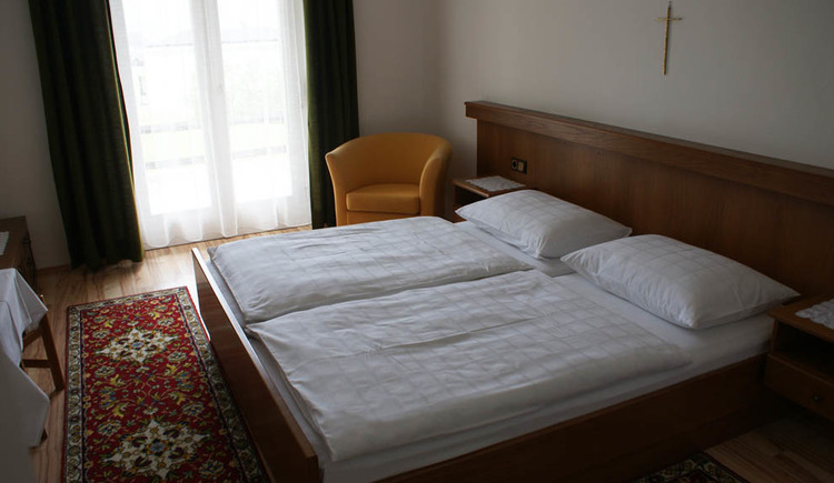 Bedroom with a double bed, in the Background a chair and the balcony door