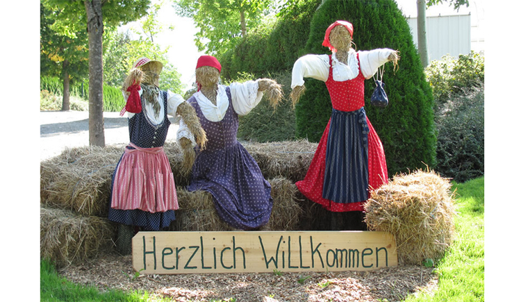 Straw bales, which heaps in dirndl dress and headscarf, sign with the inscription: Welcome