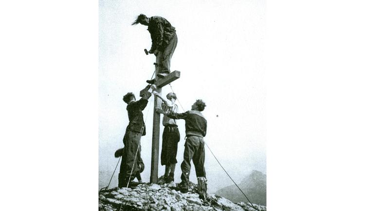 Männer montieren ein Kreuz am Berg