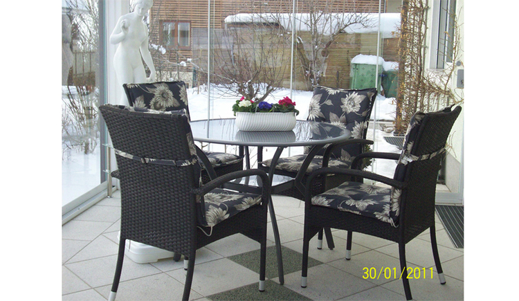 Dining area with chairs, table, in the background a statue, window with a view outside on the snowy landscape