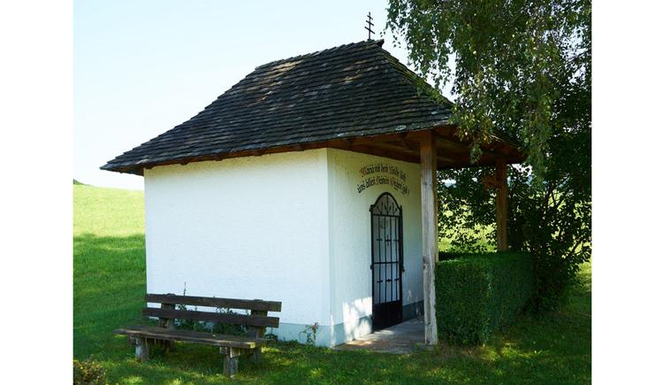 Blick auf die Kapelle, im Vordergrund eine Holzbank in der Wiese, seitlich ein Baum
