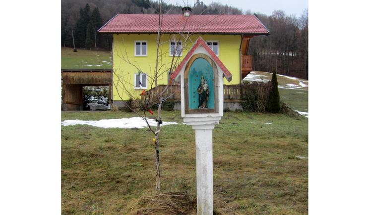 Blick auf das Marterl in einer Wiese mit einer Heiligenfigur, im Hintergrund ein Haus, Wald