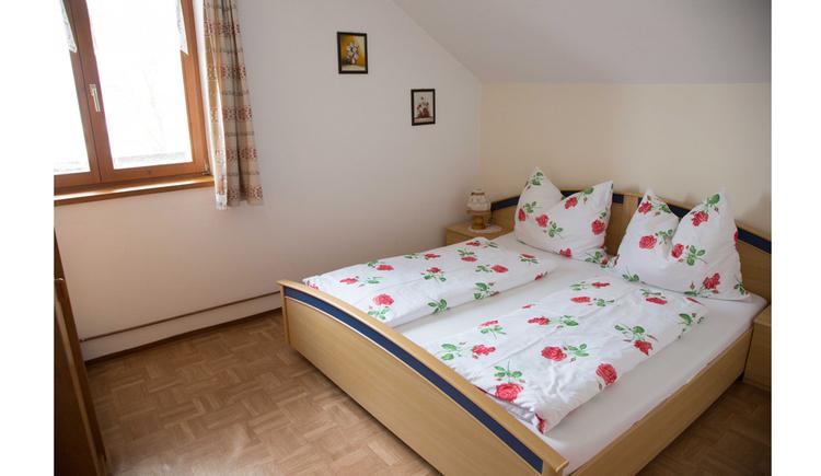 Schlafzimmer mit Doppelbett, Fenster im Hintergrund