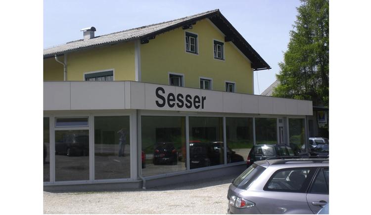 Blick auf das Autohaus, im Vordergrund seitlich Autos. (© Tourismusverband MondSeeLand)