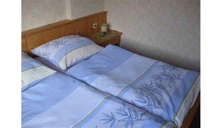 Schlafzimmer mit Doppelbett, Nachtkästchen und Tischlampe. (© Knoblechner)