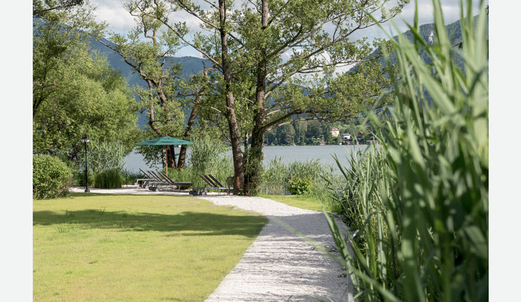Path to the beach, deckchairs, parasol, trees, shrubs, in the background the lake and the mountains