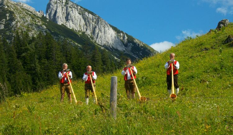 Alpenhorn musician perform during the Alm Musi Roas festival (1st Sunday in July each year) in front of the Donnerkogl summit, Gosaukamm massif