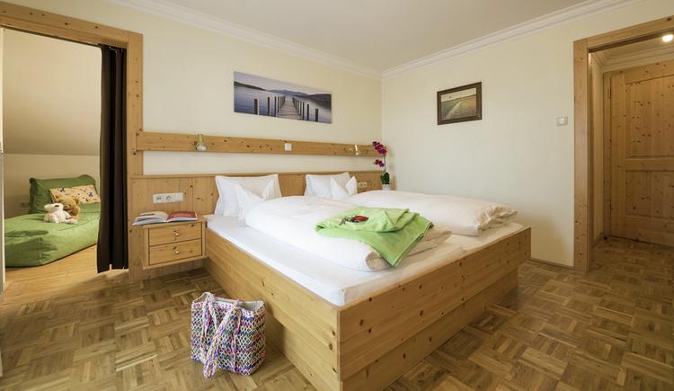 Zimmer mit Doppelbett und Verbindungstür zum Kinderzimmer. (© Familie Ragginger/Klaus Costadedoi)