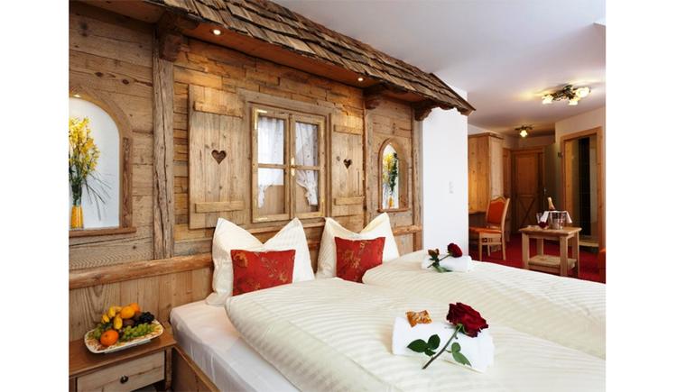 Schlafzimmer mit Doppelbett, auf dem Bett Rosen, Nachtkästchen mit gefüllter Obstschüssel, im Hintergrund Wand verkleidet mit Holz wie eine Hütte, mit Fenster, Dachschindel, im Hintergrund Rollwagen und Sessel