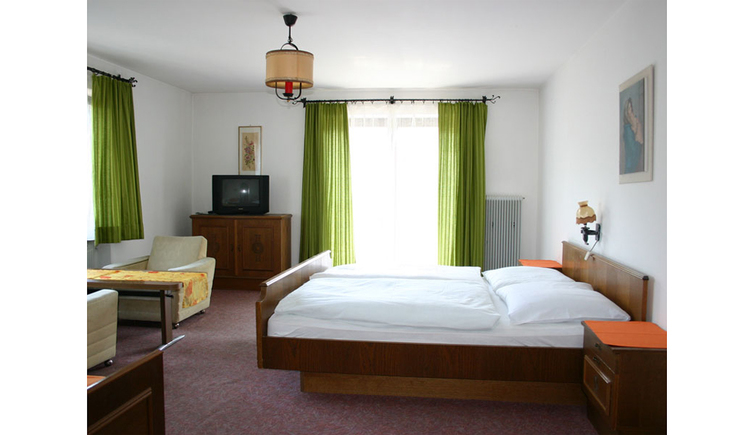 Room with double bed, nightstand, side table with chairs, in the background a chest of drawers with a TV, balcony