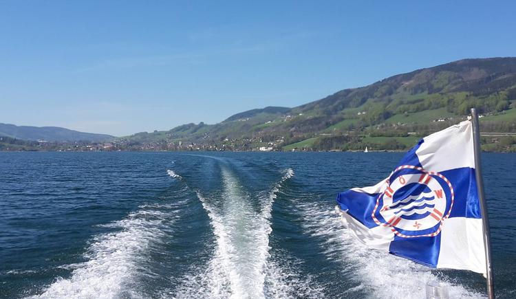 Blick vom Boot auf den See, im Hintergrund die Landschaft, seitlich ein Fahne