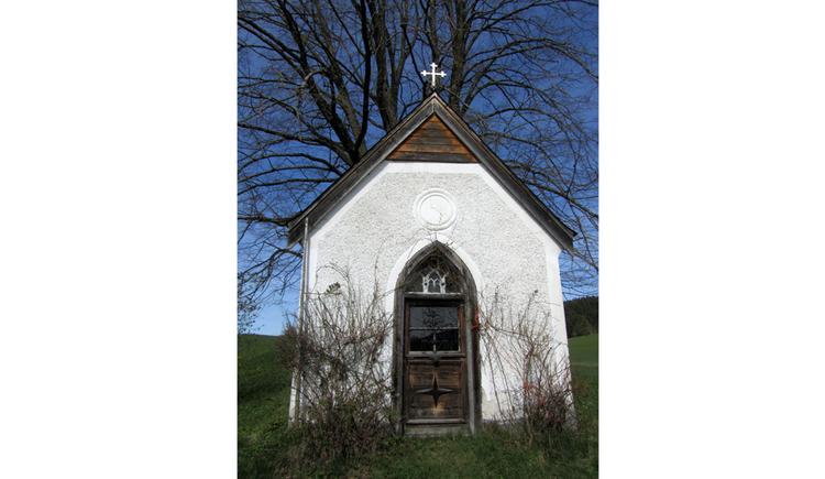 Blick auf die Kapelle, im Hintergrund ein kahler Baum