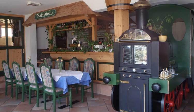 Innenbereich mit Tischen und Stühlen, und einer Lokomotive