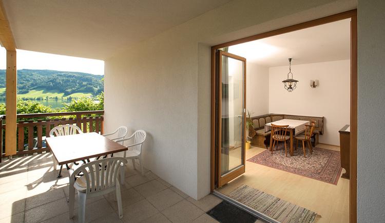 Ausblick von der Terrasse mit Tisch und Stühle in den Wohnbereich mit Eckbank, Tisch und Stuhl