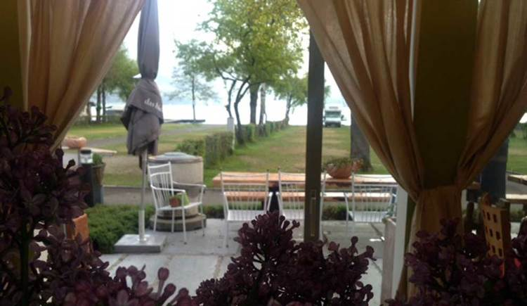 look through a window to the lake, outside is a table with chairs