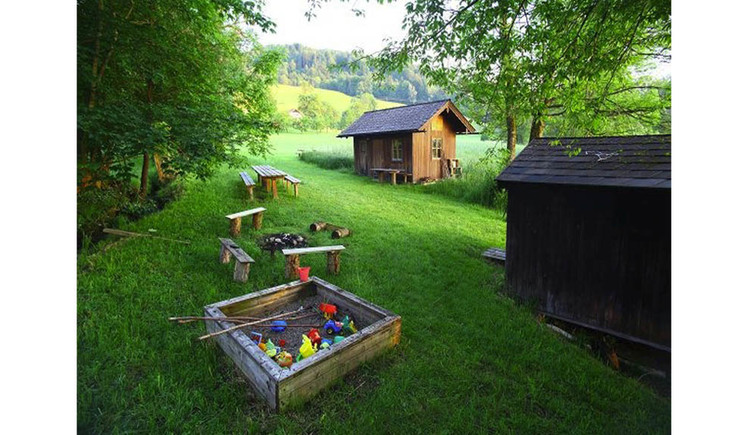 Bathing place with hut, sandbox, benches, camp fire, wooden huts, trees