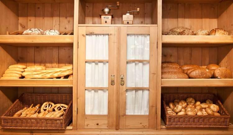 eine Holzwand mit einige Fächern, in diesen befinden sich verschiedene Brot Sorten. (© Bäckerei Berger)
