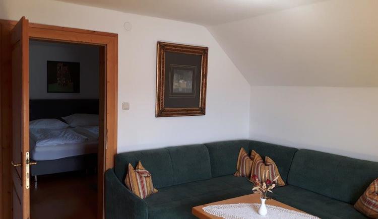 Sitzecke mit Schlafzimmer im Hintergrund