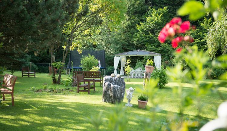 Garten mit Bänken, Blumen, im Hintergrund ein Pavillon mit Tisch und Stühlen, Trampolin