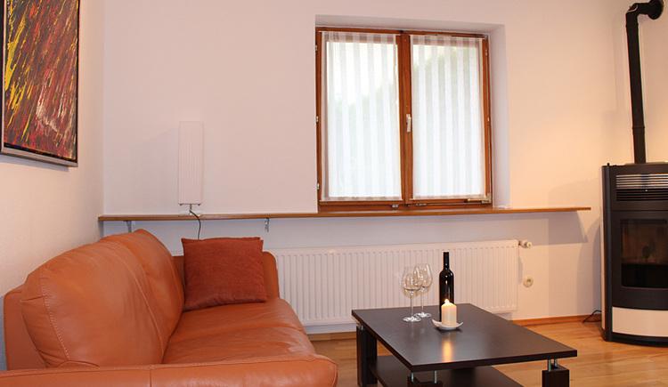 oranges Sofa davor Tisch mit Weingläsern, einer Flasche Wein und Kerze, rechts im Eck ein Kamin