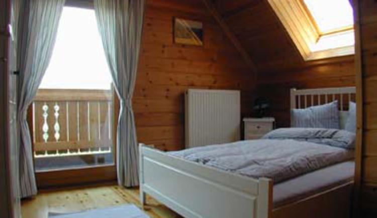 Schlafzimmer mit Doppelbett, Dachfenster und Balkon. (© Rehn)