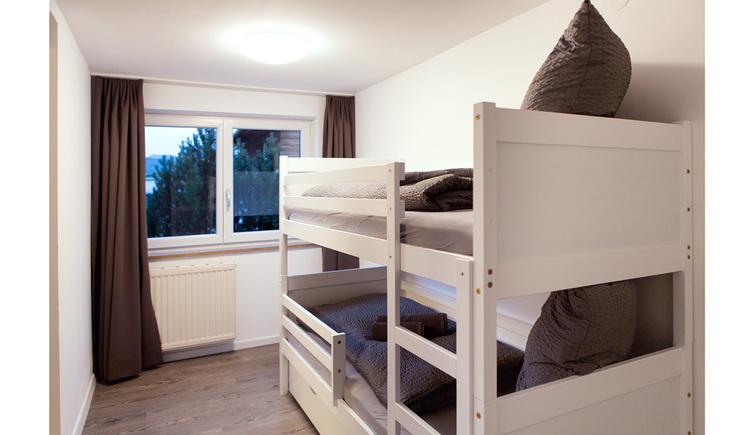 Schlafzimmer mit Stockbett, im Hintergrund ein großes Fenster