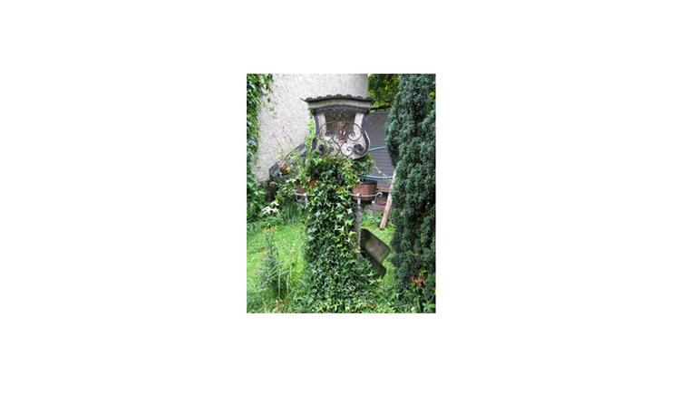 Blick auf den Bildstock verwachsen von einer Pflanze, im Hintergrund eine Mauer
