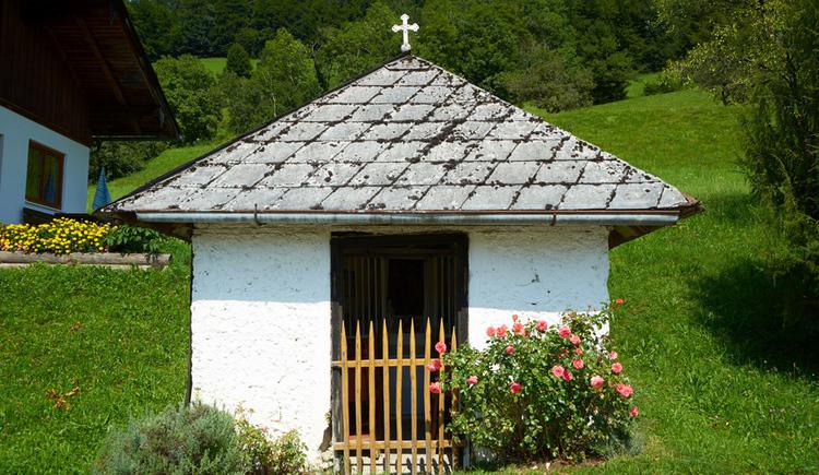 Blick auf die Kapelle mitten in einer Wiese