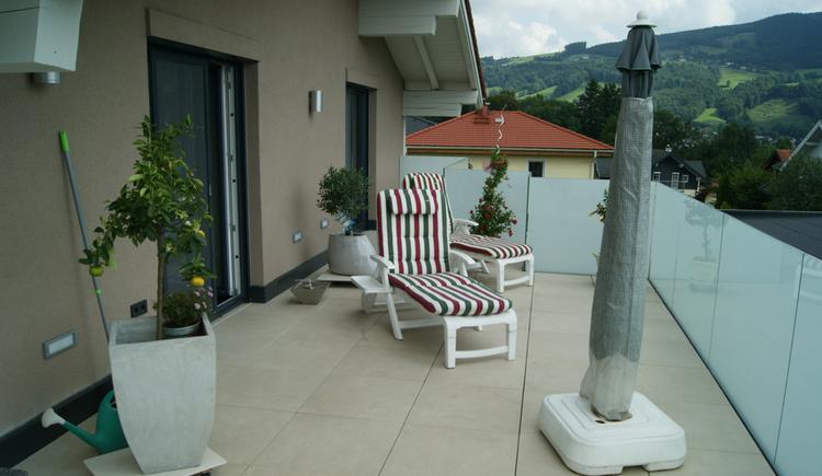 Terrasse mit Liegestuhl, Sonnenschirm, Zitronenbaum in einem Topf