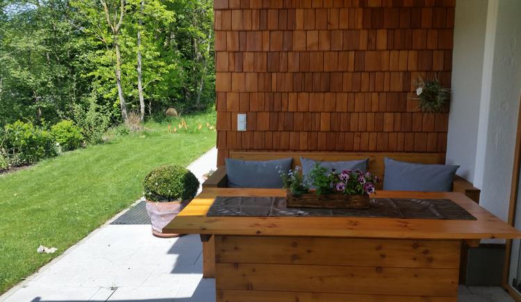 Tisch mit Bank, seitlich ein Garten, Bäume. (© Tourismusverband MondSeeLand)