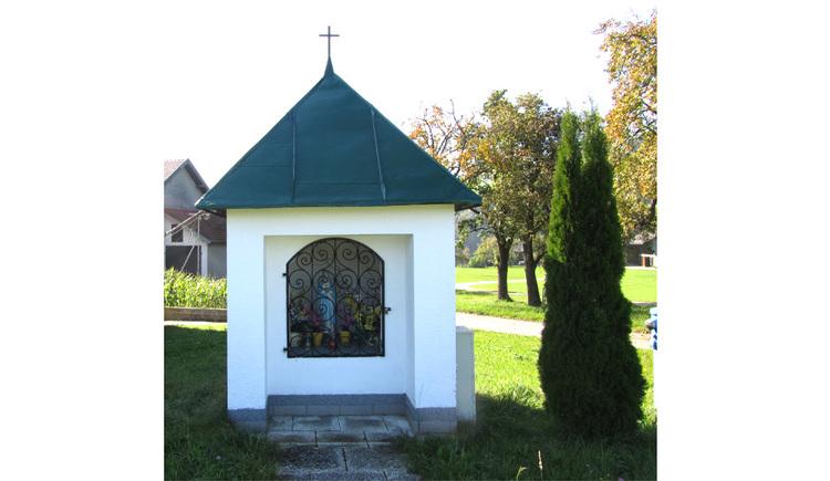 Blick auf die Kapelle, seitlich ein Baum, im Hintergrund Bäume