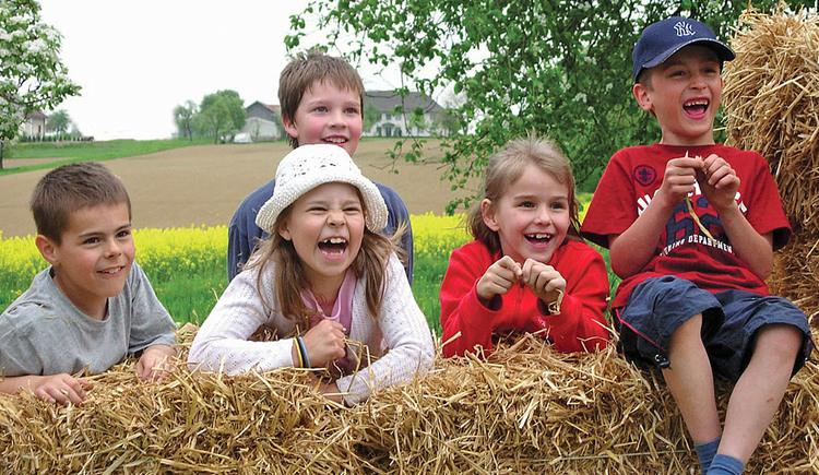 Lachende Kinder sitzen auf Heuballen