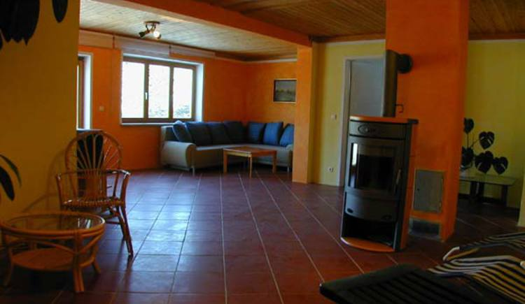 Das Wohnzimmer im Untergeschoss ist mit einer Sitzgarnitur, TV, Kamin und Relaxliegen ausgestattet. (© Rehn)