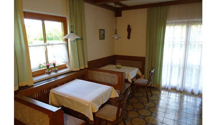 Tische, Bänke, Sessel, seitlich ein Fenster, im Hintergrund eine Balkontür
