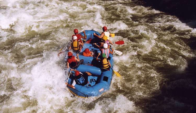 Here you will see a group of rafters in a blue rafting boat along river Traun.