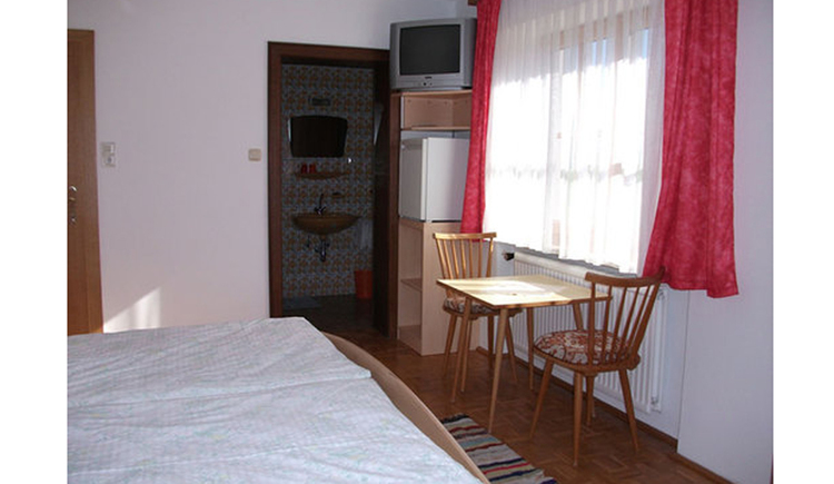 Bedroom with doublebed, table, chairs, TV and a big window. In the background the bathroom is visible.