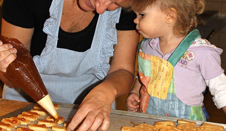 Großmutter Christine Frauendorfer lehrt ihrer Enkeltochter das verzieren von Backwaren