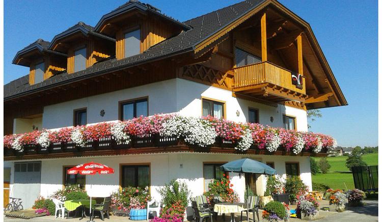 Blick auf das Haus mit Balkon und Blumen, im Vordergrund Tische und Stühle, Sonnenschirme