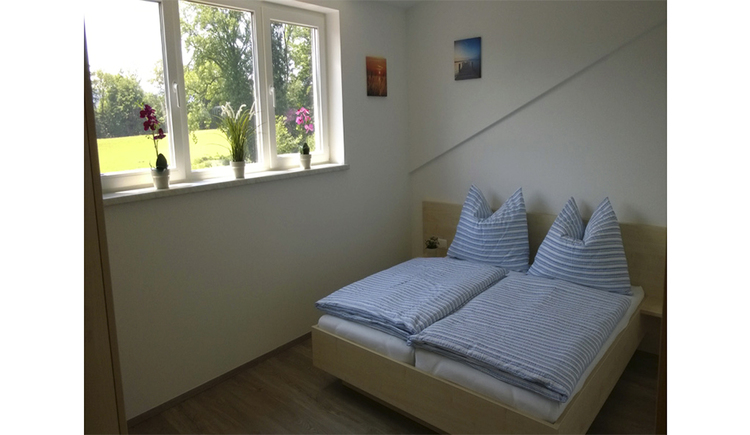 Bedroom with double bed, on the side a window with garden view