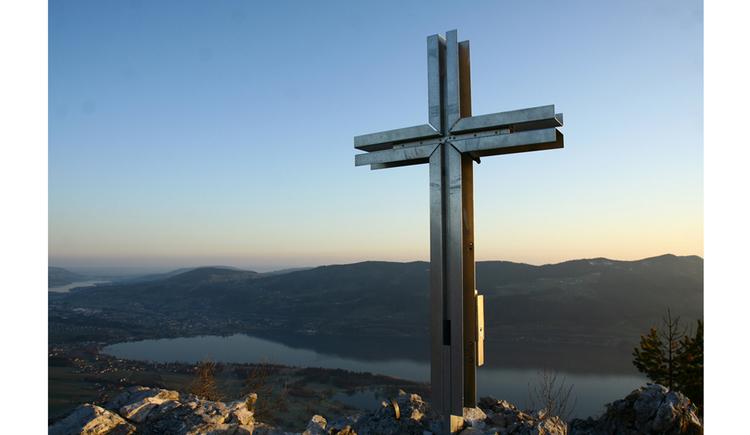 Blick auf das Kreuz, im Hintergrund ein See und Berg