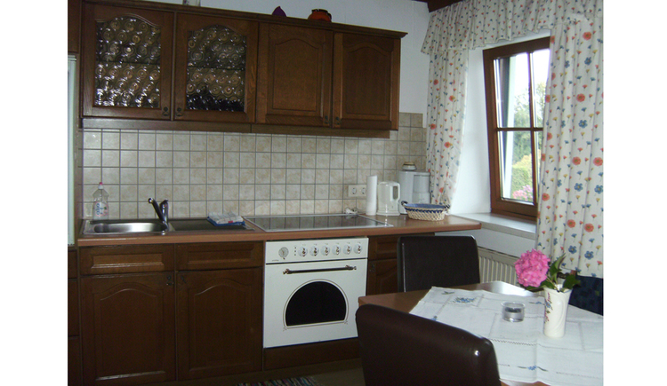 kitchen with sink, cooker, kettle, coffee machine, on the side a window, table and chairs, flower vase on the table