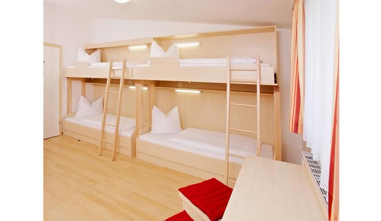 Schlafzimmer mit einzelnen Stockbetten mit Leiter, seitlich ein länglicher Tisch mit Hocker