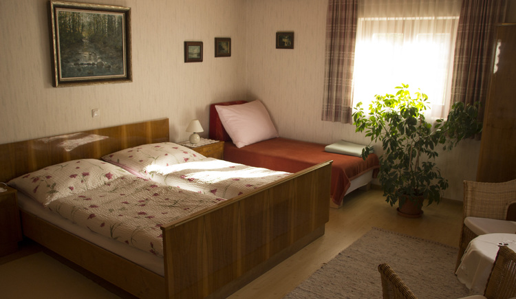 The spacious bedroom has a double bed and an extra bed