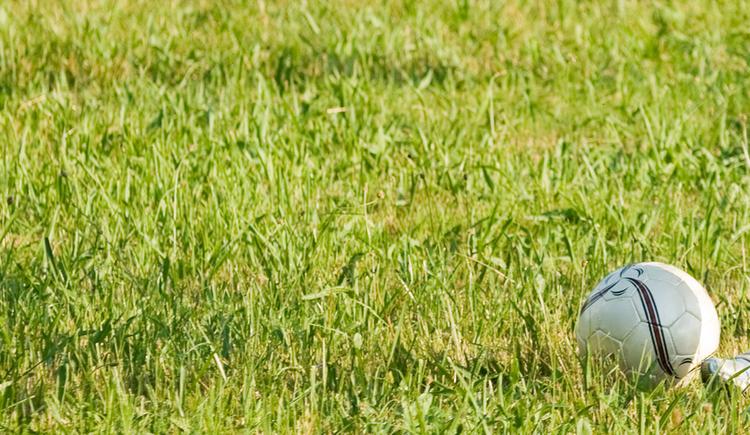 Rasen mit Fußball und Spitze eines Schuhs. (© www.mondsee.at)
